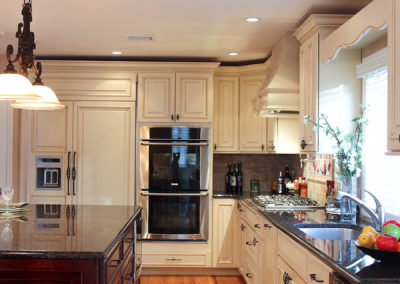 All colors present - light wood floors, dark wood island and off-white cabinets make a beautiful classic blend
