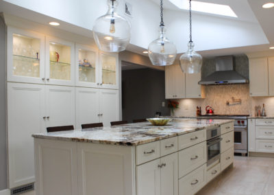 Everything beautiful all in one kitchen -gorgeous Blanc de Blanc granite countertop, high ceilings with sky lights, hanging clear bowl light fixtures and beautiful white cabinets all around