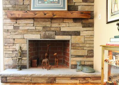 Cultured stone fireplace with stone slab base shelf