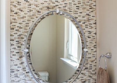 Stacked stone accent wall with oval mirror