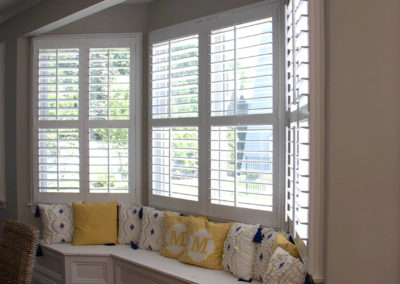 Bright sunny window seat with lots of comfy pillows