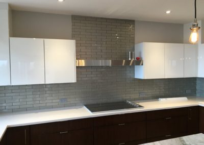 Hi-gloss white cabinets and glass subway tile backsplash with white quartz countertop